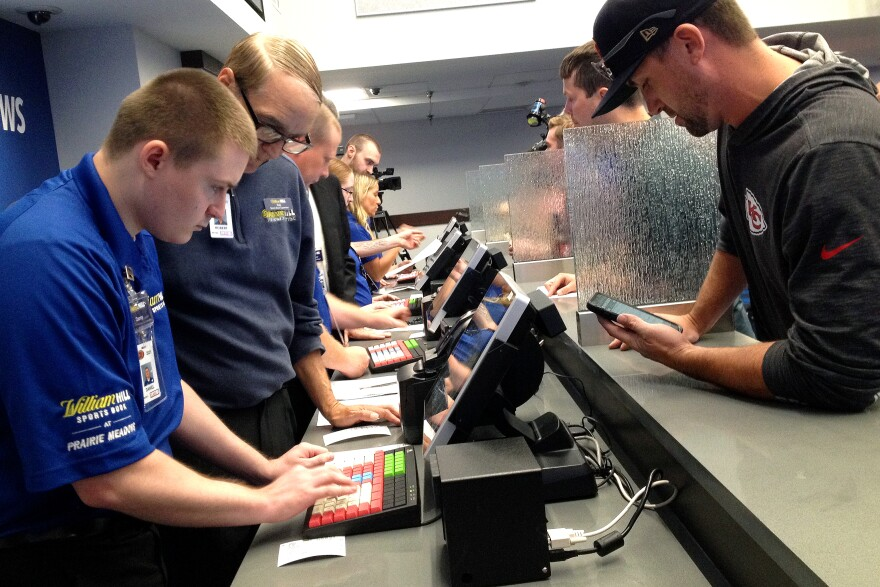Workers at Prairie Meadows in Altoona, Iowa, take the first bets at the casino's new sportsbook.