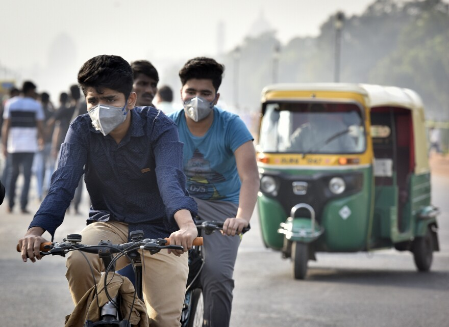 Commuters in New Delhi wear face masks amid a layer of smog.