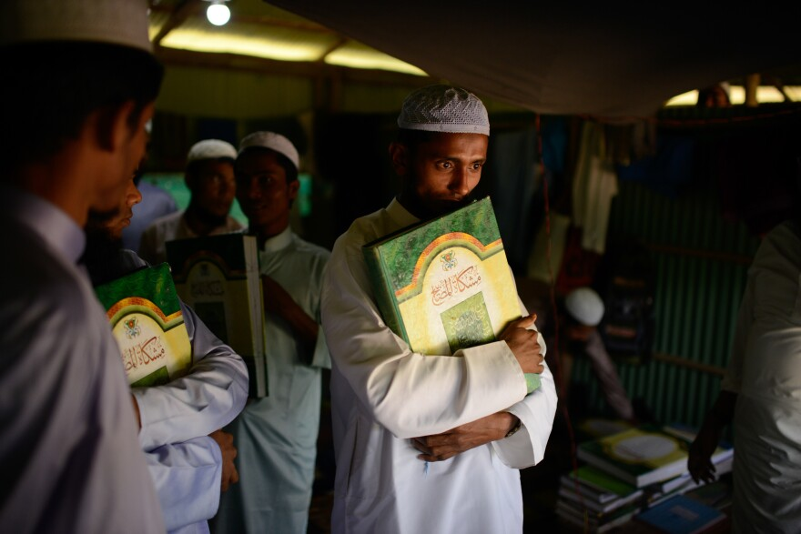 A student holds an Islamic text at a madrassa in the Kutupalong Rohingya refugee camp. With limited educational opportunities for children in the camps, many Rohingya families are sending their kids to madrassas to study Arabic and Islamic studies.