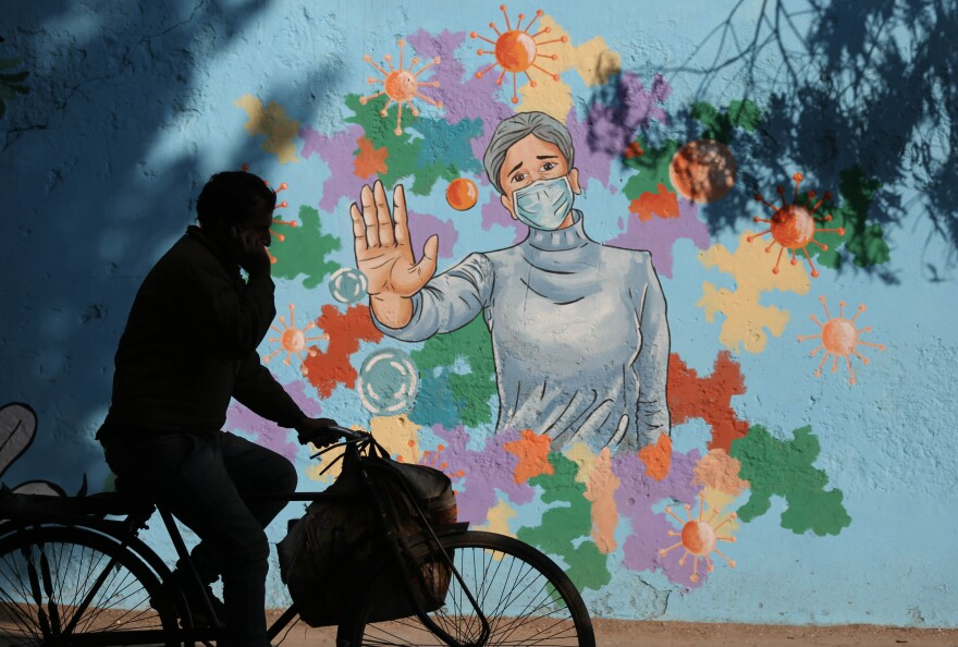 A mural in New Delhi is part of public health messaging in India. The country has seen a dramatic decline in new cases since fall, but researchers aren't sure why.