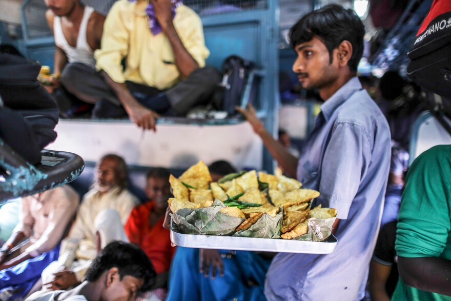 A vendor sells fried snacks on a train in northern India. Food vendors are a regular presence on most trains, jumping on and off trains at various stations, offering passengers a welcome snack break during their long journeys.