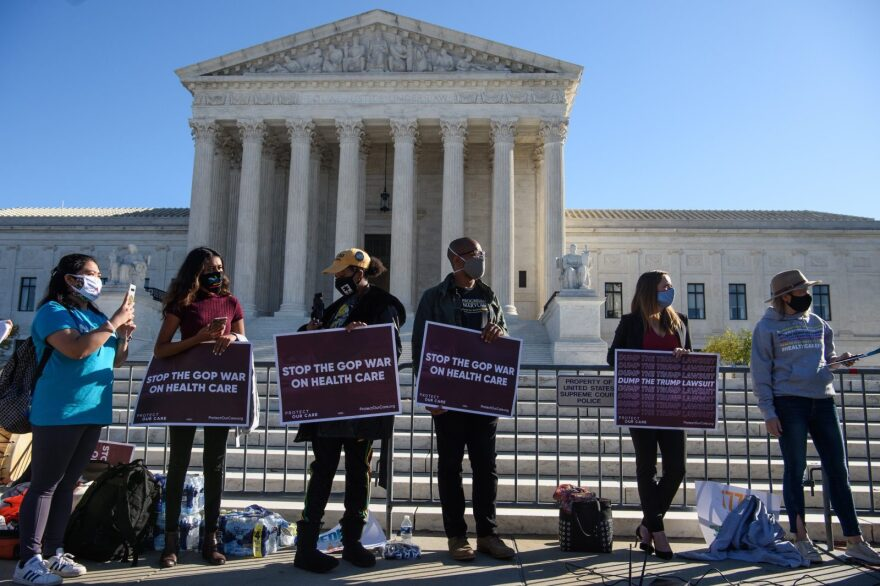 Demonstrators hold signs in front of the US Supreme Court in Washington, DC, on November 10, as the high court opened arguments in the long-brewing case over the constitutionality of the 2010 Affordable Care Act.
