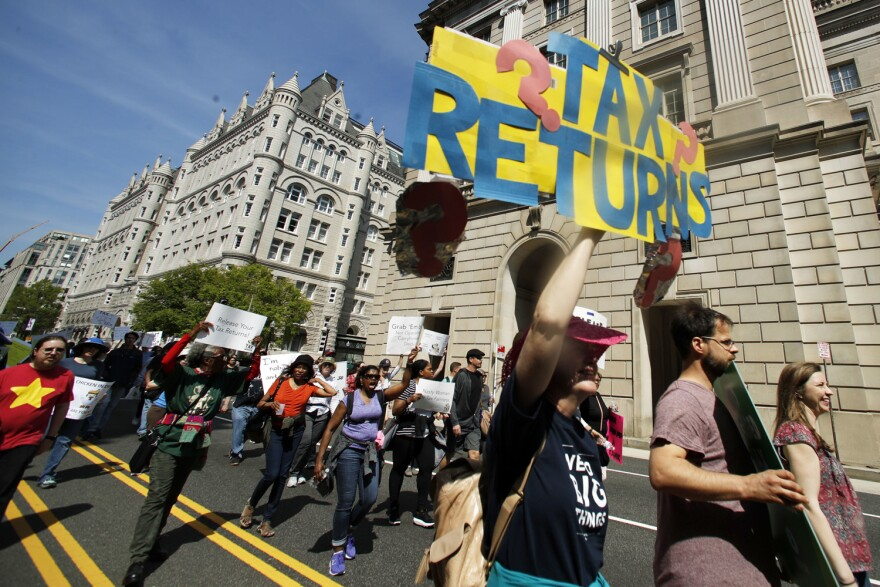 Protesters march past the Trump International Hotel, backround left, and the Internal Revenue Services building, right, during a Tax Day demonstration in Washington, Saturday, April 15, 2017, calling on President Donald Trump to release his tax returns. (Manuel Balce Ceneta/AP)