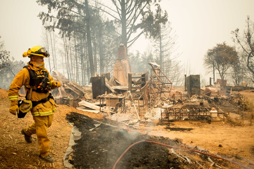 Alameda County firefighter Wally Armstrong cools down hot spots in front of a residence leveled by the Loma fire near Morgan Hill, Calif., on Wednesday.