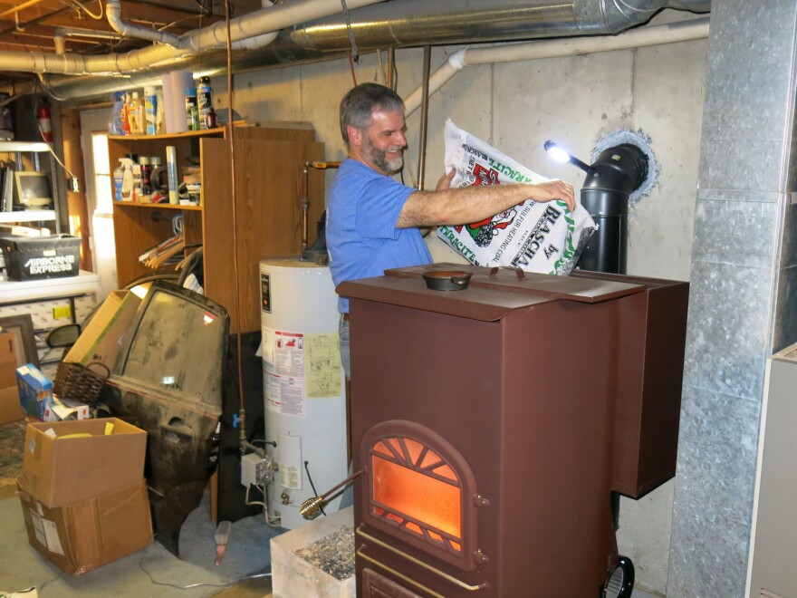 Ord loads a hopper on the back of his coal-burning stove. He says 400 pounds of coal will keep his 2,400-square-foot house between 70 and 72 degrees for a couple of weeks in the winter.