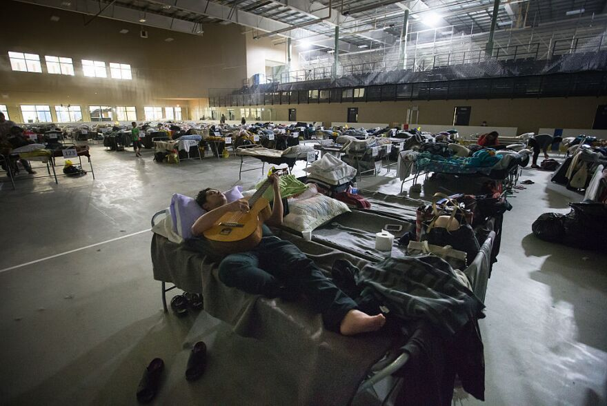 A Fort McMurray evacuee plays a guitar while lying on a cot at a hockey rink in Lac La Biche, Alberta, Canada, on Saturday.