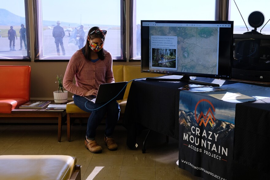 """A woman types on a laptop on her lap next to a poster that reads """"Crazy Mountains."""""""
