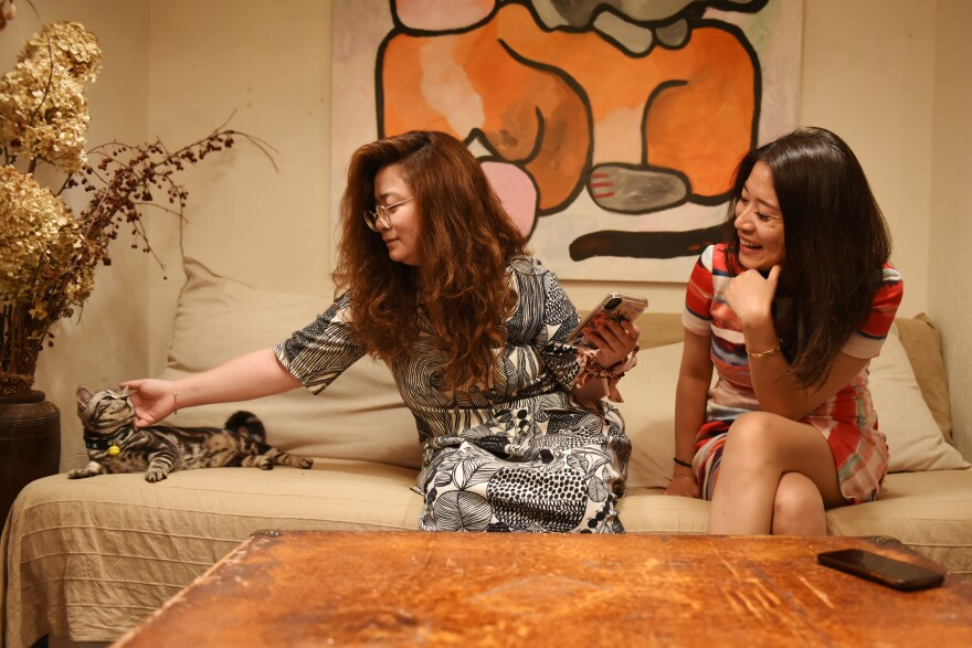 Affluence means free time for many members of Beijing's professional class. Wendy Wang (left), 29, and Delicia Kuang, 32, kick back after work at a cat cafe in a trendy neighborhood in China's capital.