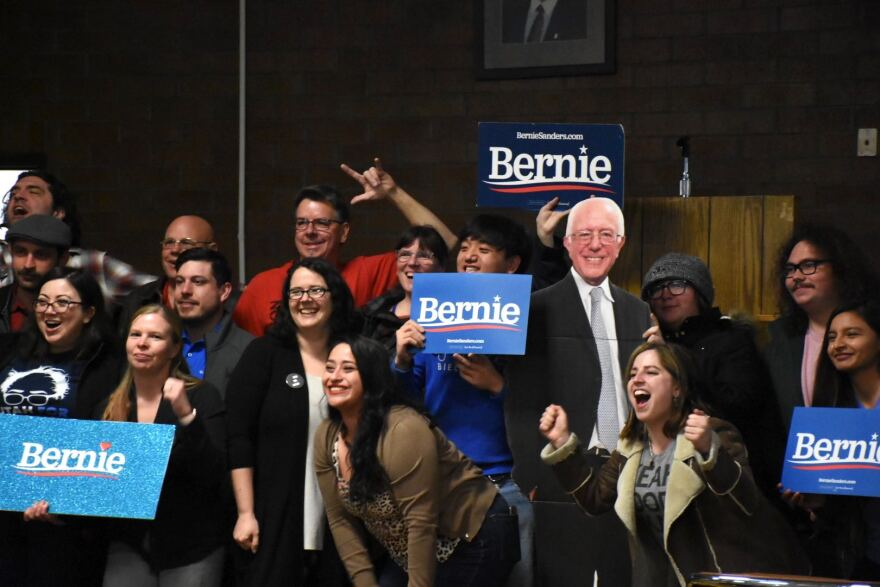"""Photo of Bernie Sanders supporters holding signs that read """"Bernie"""" next to a cardboard cutout of Sanders."""
