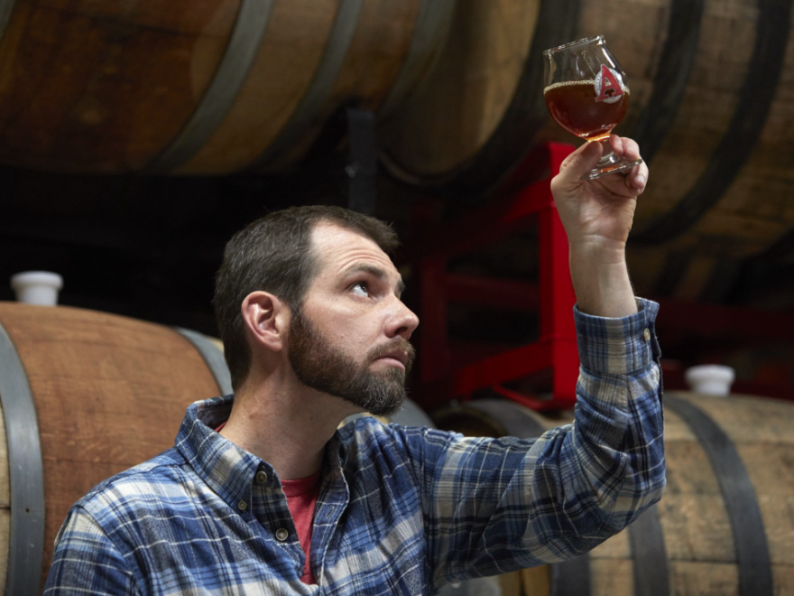 """Beer archaeologist Travis Rupp inspects his latest """"Ale of Antiquity,"""" George Washington Porter, surrounded by the oak barrels it fermented in at Avery Brewing Co. in Boulder, Colo."""
