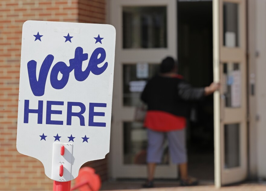File photo of polling worker as she enters a polling place in Charlotte, N.C., Wednesday, April 24, 2019 as early voting began in the Republican primary election for the North Carolina 9th Congressional District, a special election that was forced after last year's race was voided by a ballot-collection scandal.