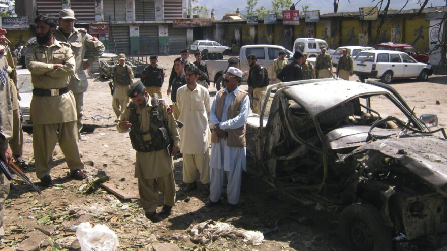 Pakistani security officials inspect wreckage from a suicide attack at a bus stand in the district of Lower Dir on Monday.