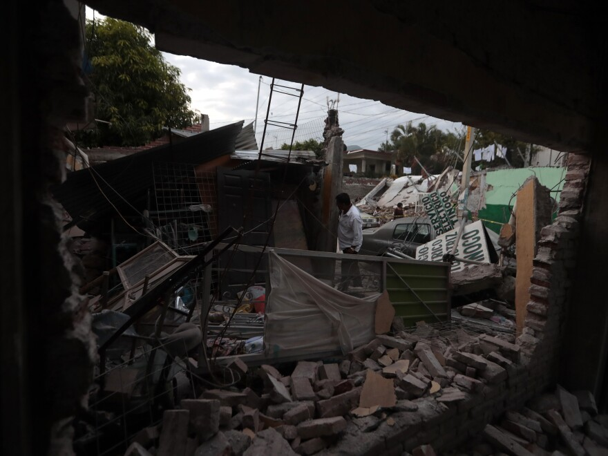 A man surveys a building demolished by the earthquake in hard-hit Jojutla in the state of Morelos. Dozens of people died in the state, which felt some of the worst of the temblor's effects.