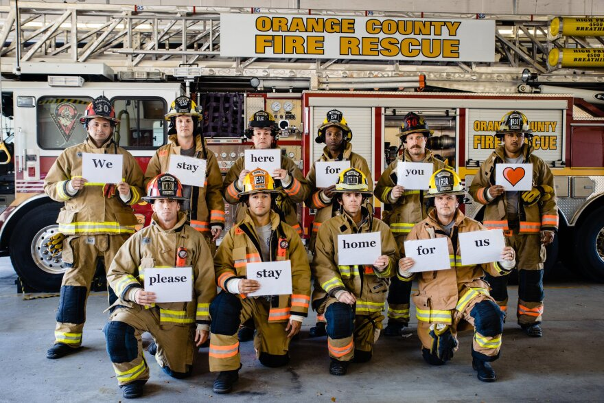 "Orange County firefighters hold up signs that read ""We stay here for you, please stay home for us."""