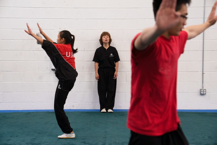 Zhang coaches from the sidelines as students stretch before practice.