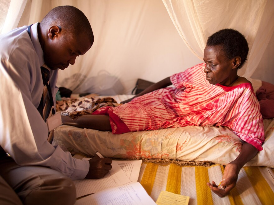 An HIV-positive woman, living alone in a one-room house, speaks with a visiting doctor.