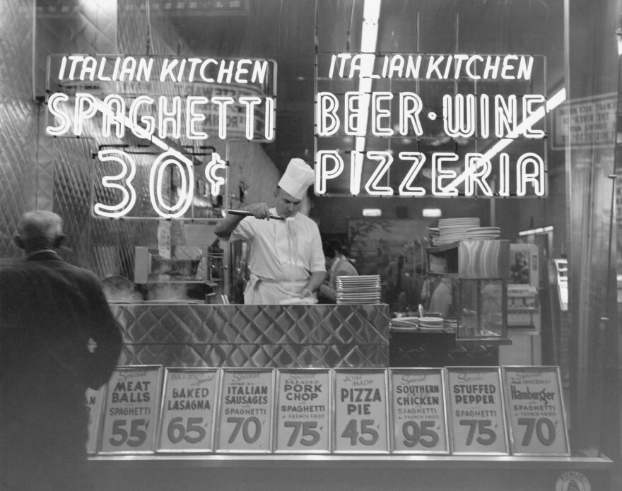 """A chef cooks spaghetti at an Italian restaurant in Manhattan in 1953. In the late 19th and early 20th century, social workers and nutritionists cautioned that Italian food was too garlicky and spicy — which they said increased the craving for alcohol. It's now America's most popular """"ethnic"""" cuisine."""