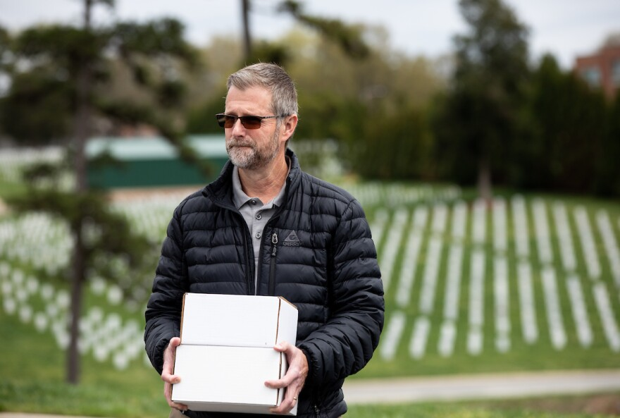 Ivar Lonon holds two boxes containing the cremated remains of his mother and father at Salisbury National Cemetery in Salisbury, N.C., on Thursday, March 26, 2020. Lonon's father was a veteran, but due to the current coronavirus pandemic, VA cemeteries will not allow traditional military funerals to take place. Instead, only Lonon and his wife were allowed at the burial site, where the boxes containing the remains were wrapped in plastic bags and buried with no ceremony.