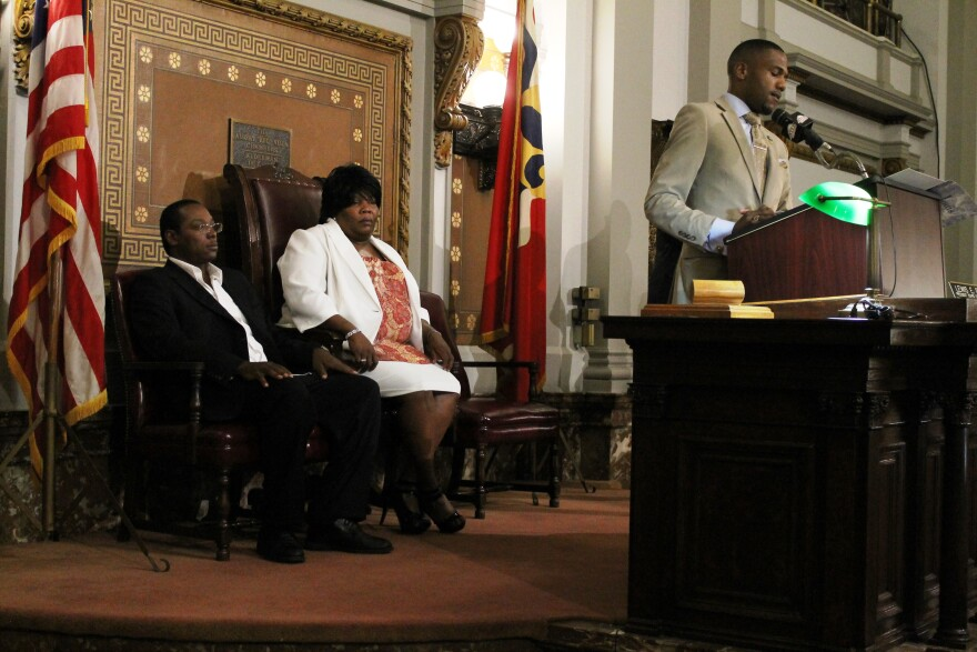 Alderman John Collins-Muhammad, D-21st Ward, speaks as Anthony Lamar Smith's parents, Annie Smith and Darvell Smith Sr., look on.