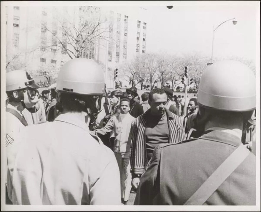 A black and white photograph showing protesters facing law enforcement officers wearing helmets and gas masks whose backs are to the camera.
