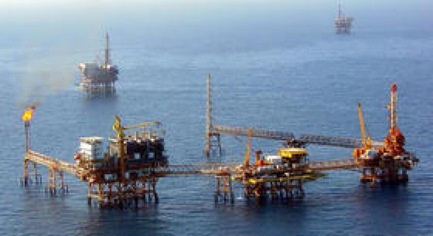 Drilling platforms off a Mexican shoreline are pictured.