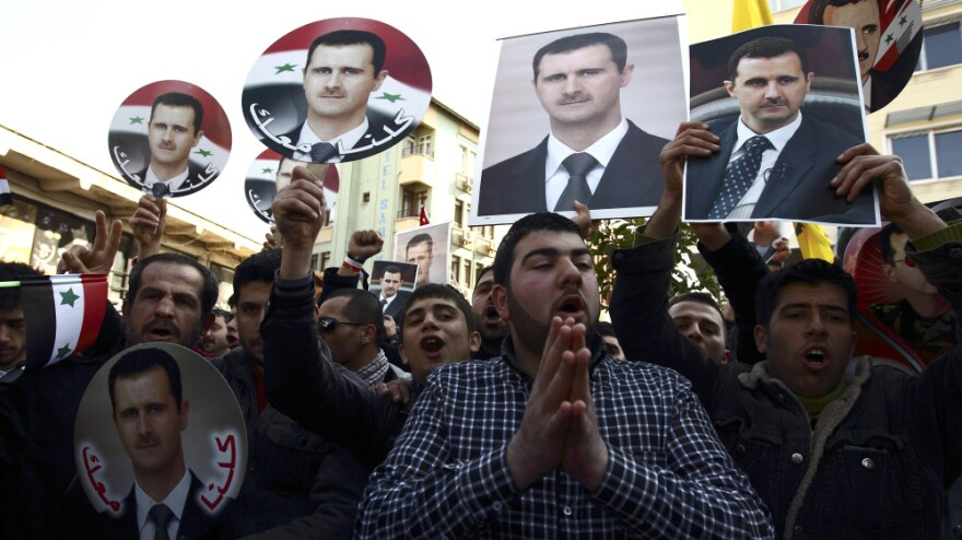 Syrians and Turks show their support for Syrian President Bashar Assad in Turkey's southern city of Antakya on Feb. 19. Assad is a member of the minority Alawite religious sect, and many Alawites on both sides of the border support him.