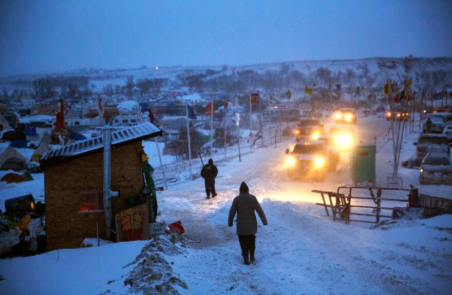 A motorist checks the condition of an exit ramp before attempting to drive out of the Oceti Sakowin camp tonight.