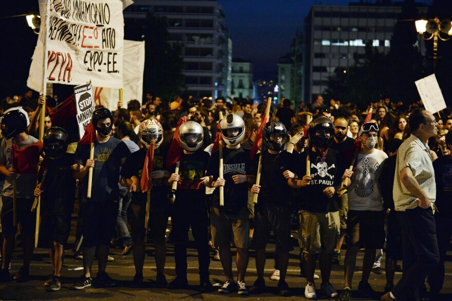 Protesters stand in front of thre Greek parliament in Athens during an anti-austerity protest on Wednesday.