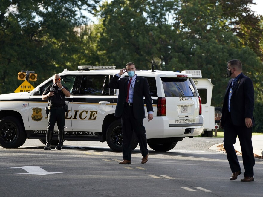 Members of the U.S. Secret Service stand outside Walter Reed National Military Medical Center in Bethesda, Md., before President Trump arrives Friday.