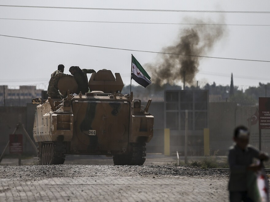 Fighting continued early Friday in a northeast Syrian border town at the center of the fight between Turkey and Kurdish forces, despite a U.S.-brokered cease-fire that went into effect overnight.