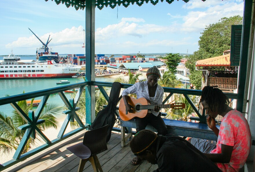 """Students at the Dhow Countries Music Academy, dedicated to preserving the music known as """"taarab,"""" play on a balcony overlooking Zanzibar's port."""