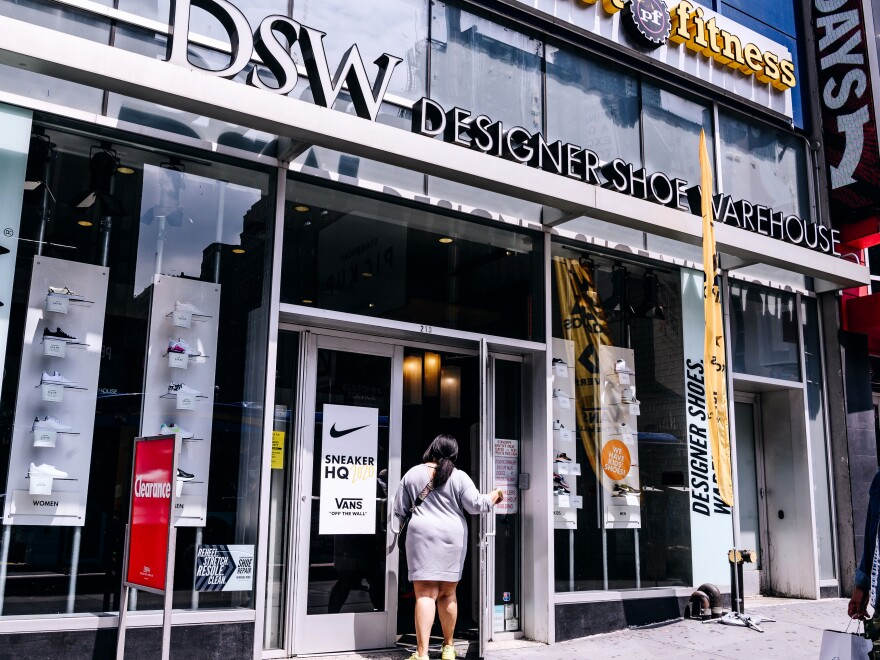 A shopper enters a Designer Shoe Warehouse store in New York City. DSW is partnering with Hy-Vee, a Midwest supermarket chain, to offer shoes in grocery stores.