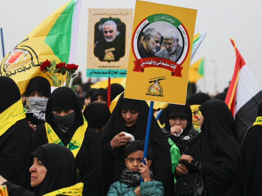 "Demonstrators hold aloft portraits of Iraqi paramilitary chief Abu Mahdi al-Muhandis and Iranian military leader Qassem Soleimani during the funeral procession Saturday in Baghdad. The crowd of thousands chanted ""Death to America"" at times."