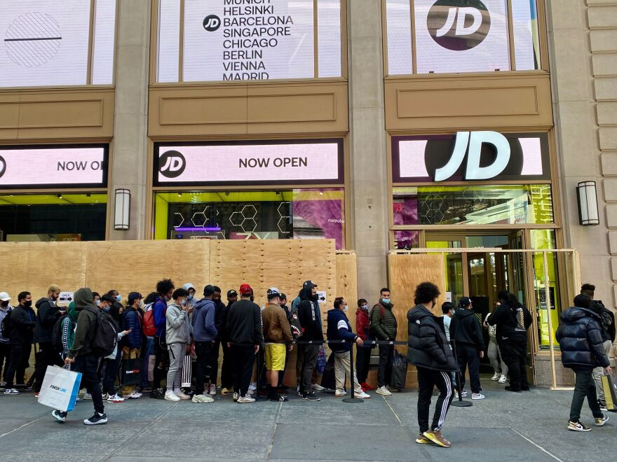 People wait in line outside for their turn to enter the JD Sports store in New York City on Nov. 5.