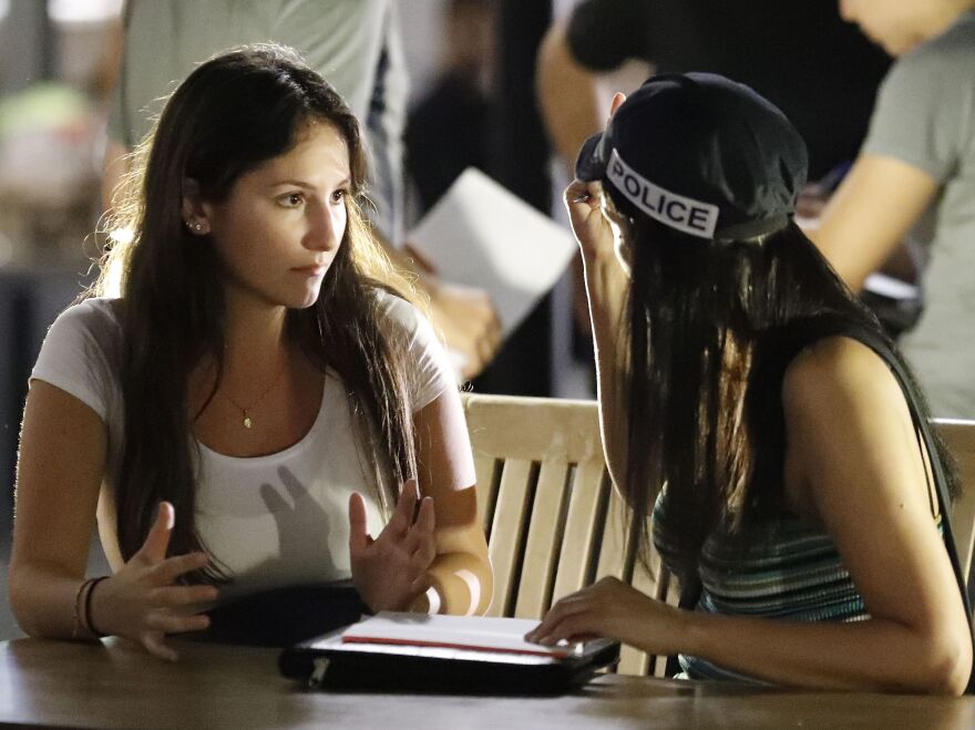 An Israeli policewoman (right) interviews a witness about the shooting attack at a shopping complex in Tel Aviv.