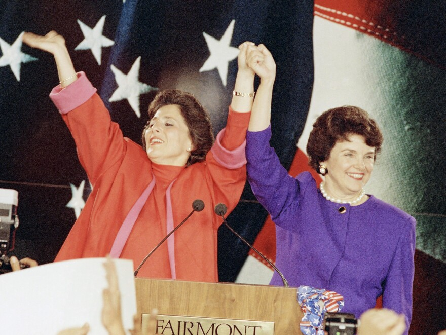 """Democratic Senate candidates Barbara Boxer (left) and Dianne Feinstein raise their arms in victory at an election rally in San Francisco on Nov. 4, 1992, the so-called """"Year of the Woman"""" in politics."""