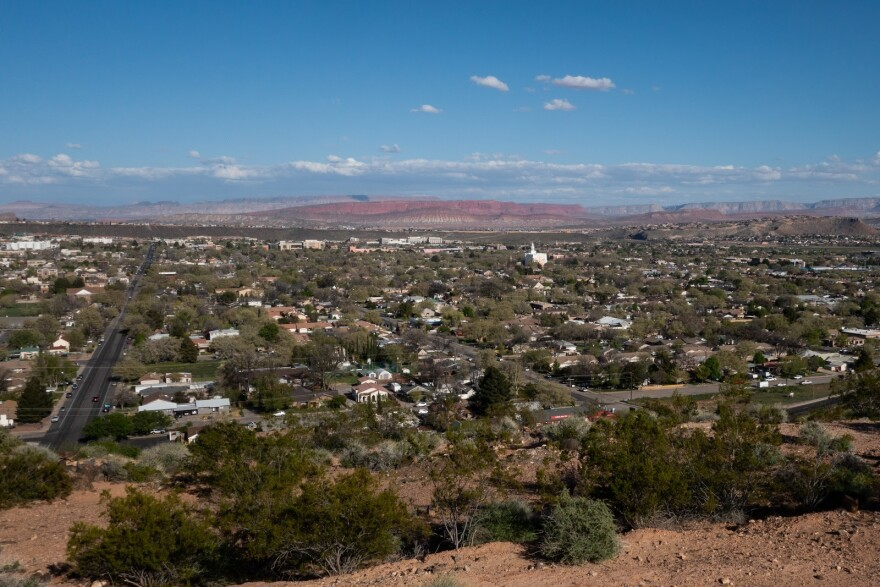 The city of St. George, seen from above. A grid of rooftops, treetops stretch out towards red cliffs in the distance.