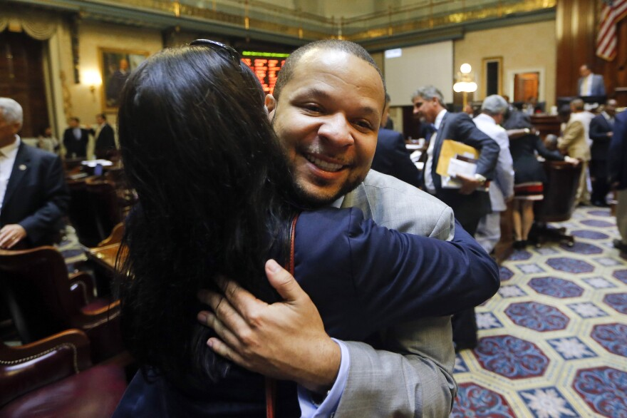 State Rep. John King, D-York, hugs a woman after the House approved a bill removing the Confederate flag from the Capitol grounds early Thursday in Columbia, S.C.