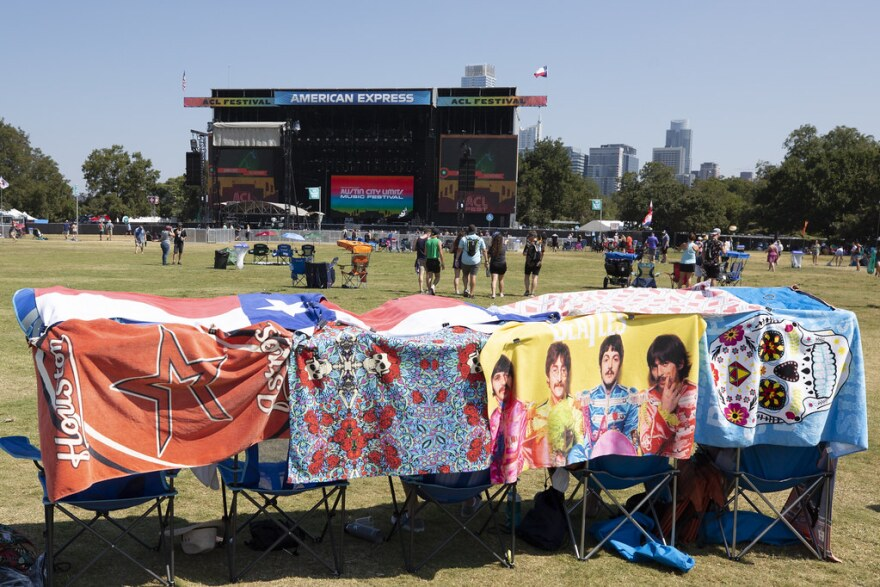 Festival-goers set up seats with towels over them as protection from the sun.