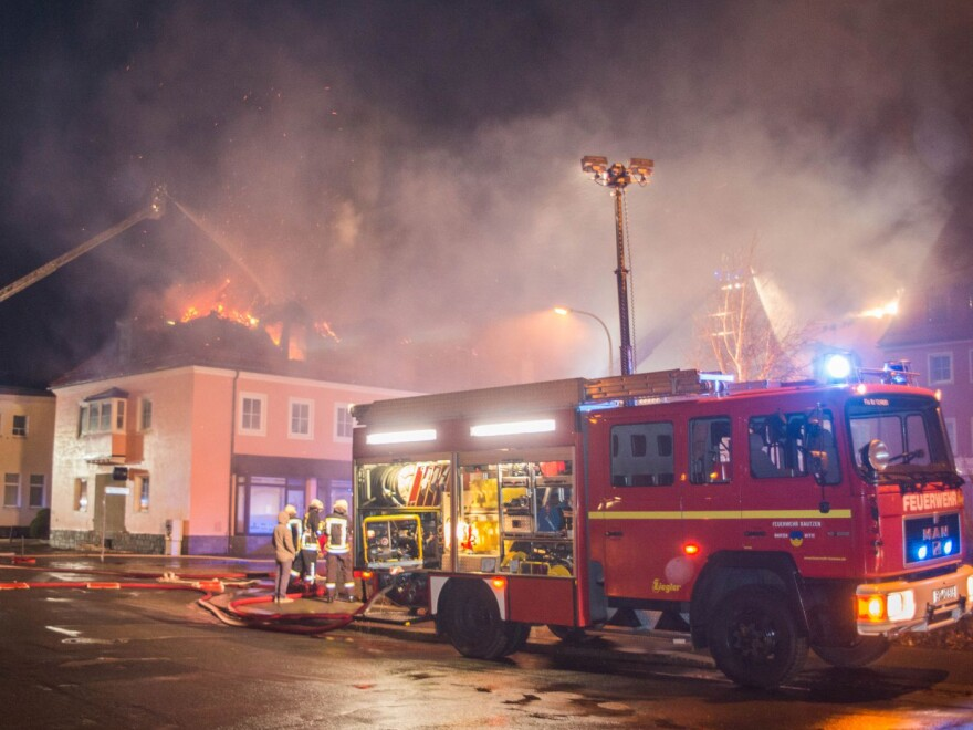 Firefighters try to extinguish a blaze Feb. 16 at a former hotel under reconstruction to become a home for asylum seekers in Bautzen, Germany. A crowd cheered and chanted anti-migrant slogans during the fire, which is being investigated as arson.