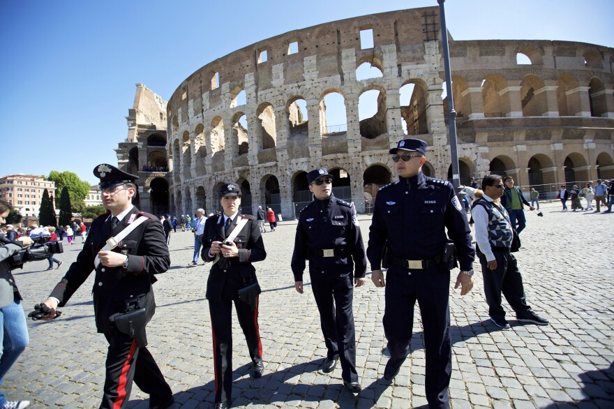 Chinese police officers (right) work with Italian police (left) outside Rome's Colosseum on May 2. Chinese police have been patrolling with Italian officers in Rome and Milan in a two-week experiment.
