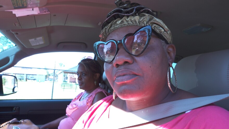 Woman with pointed glasses and a gold hat stares at the viewer while in her car.