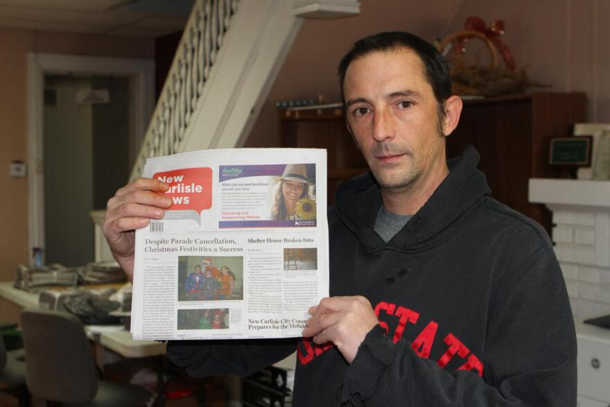 Andy Grimm holds the final print edition of the New Carlisle Times.
