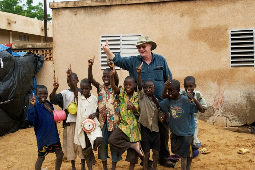 Michael Elliott poses with a group of children during a trip to Segou, Mali. One reason for his optimistic outlook is the dramatic drop in deaths of children under age 5.