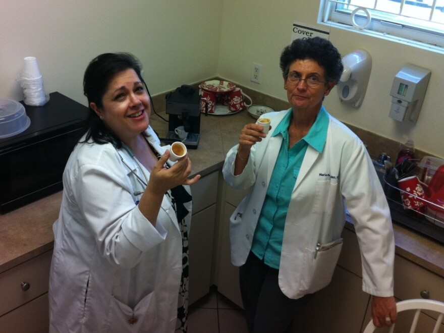(From left): Maria Torres and Maria Menendez drink Cuban coffee in Miami. Both are nurse practitioners at the San Juan  Bosco Clinic.