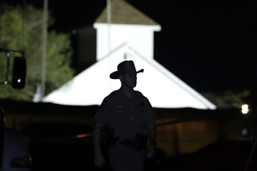 A law enforcement officer stands in front of the First Baptist Church of Sutherland Springs, where a gunman killed 26 people on Sunday.