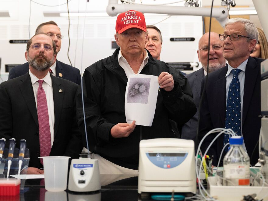 At the CDC, President Trump holds a picture of the coronavirus as top health officials take him on a tour of a lab where tests are developed.