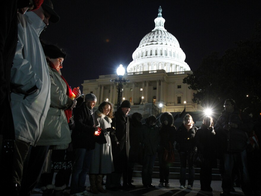 People gather for a candlelight vigil for the victims of the shooting rampage, at the steps of the Capitol in Washington on Saturday.