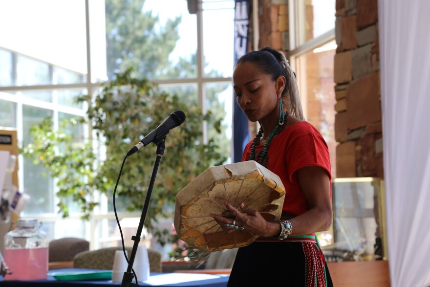 A photo of a woman in Navajo dress plays a hand drum made from animal skin.