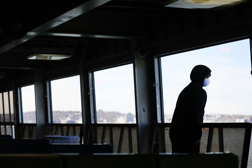 "Tremaine Fredericks rides a nearly empty Staten Island Ferry to Manhattan in New York City. Gov. Andrew Cuomo's ""New York State on PAUSE"" executive order went into effect on March 22."